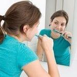 teen brushing her teeth
